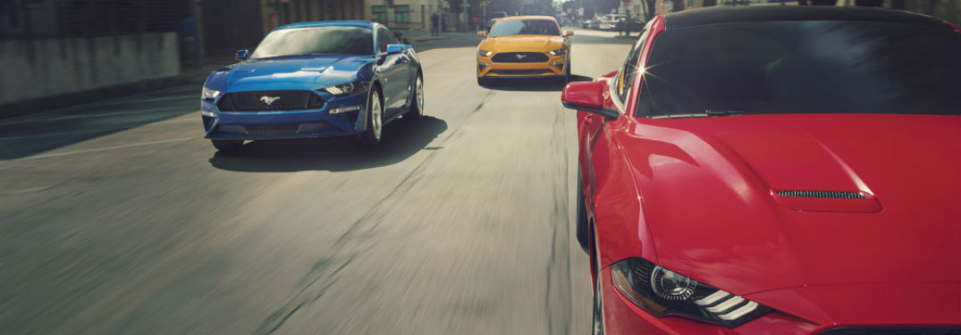 front view of a red, a blue and a yellow Ford Mustang driving down a street together