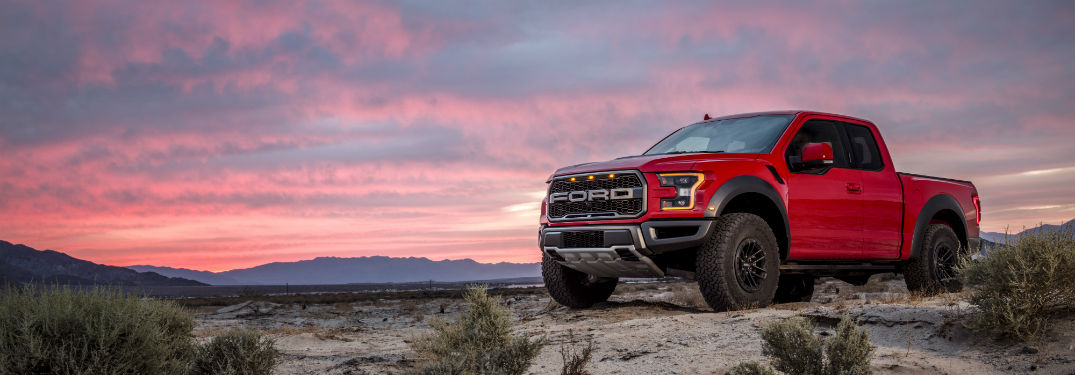 side view of a red 2019 Ford F-150 Raptor with the sunset in the background