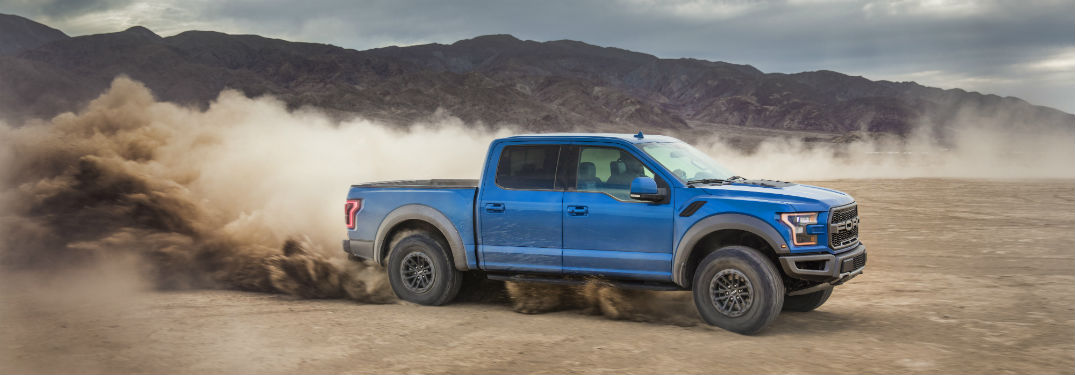 side view of a blue 2019 Ford F-150 Raptor driving off-road