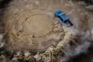 aerial view of a blue 2019 Ford F-150 Raptor doing off-road donuts