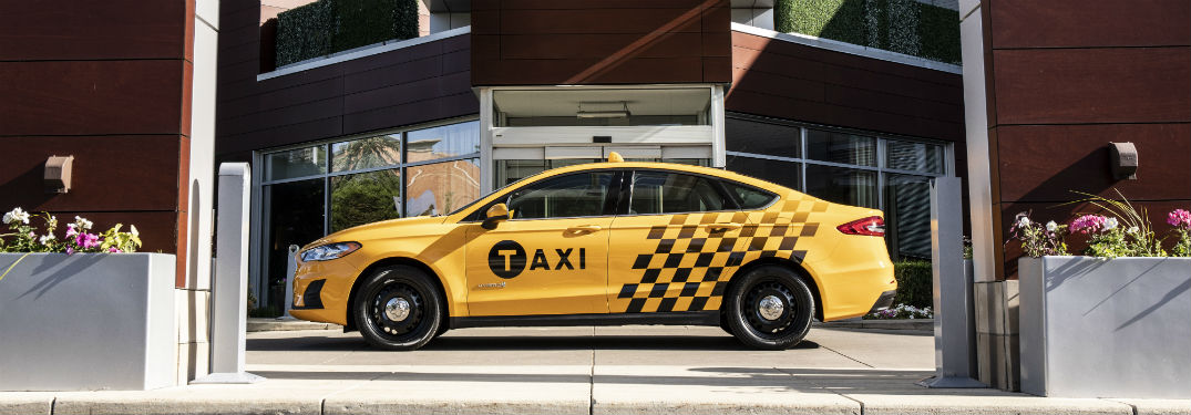 side view of a yellow 2019 Ford Fusion Hybrid Taxi
