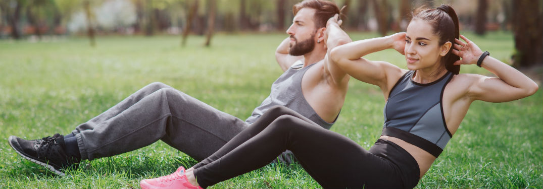 a man and a woman doing sit ups in a park