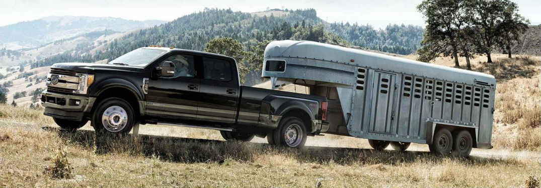 side view of a black 2019 Ford Super Duty towing a horse trailer