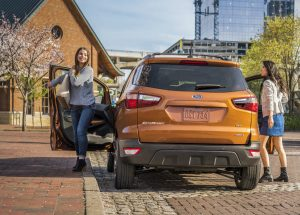 rear view of an orange 2019 Ford EcoSport with two women getting out of it