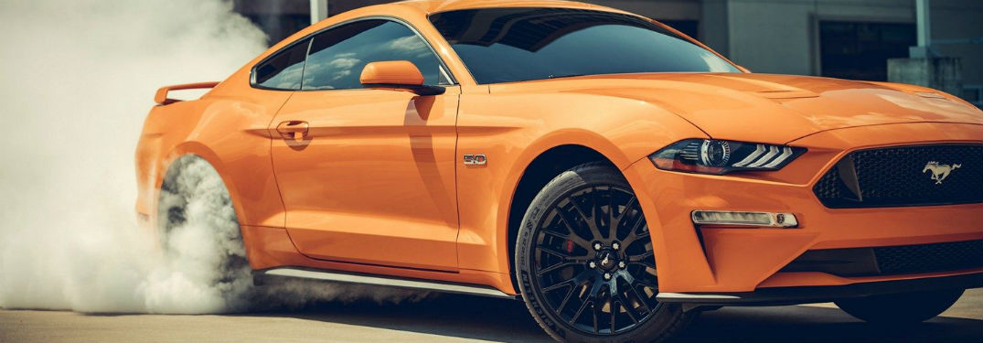 an orange 2019 Ford Mustang doing a burnout