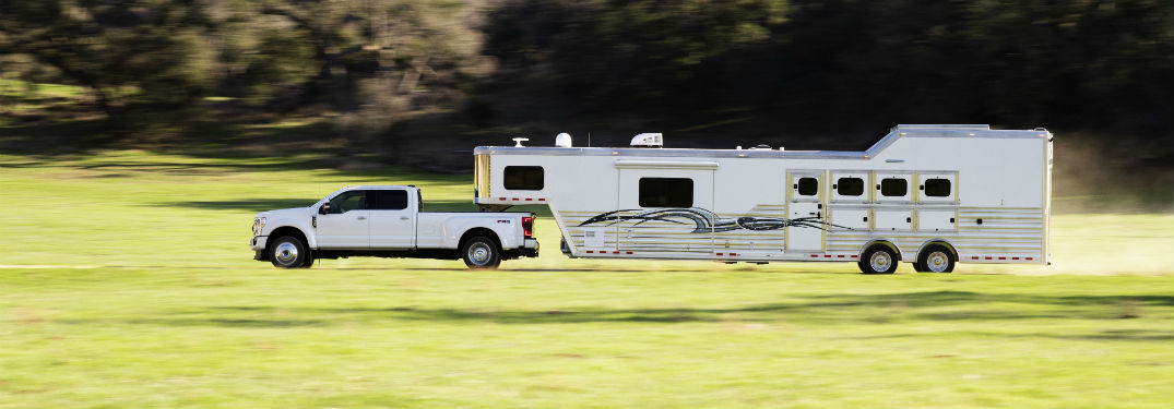 side view of a white 2020 Ford Super Duty towing a large camper
