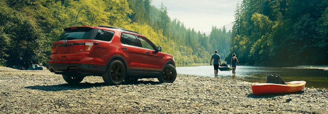 side view of a red 2019 Ford Explorer next to a river