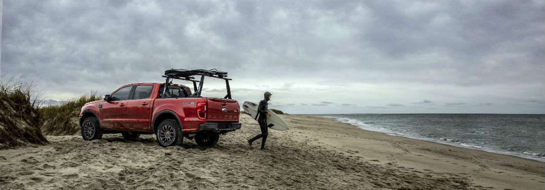 a red 2019 Ford Ranger parked on a beach with a guy walking toward the water
