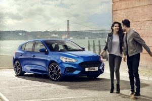 a couple standing next to a blue 2019 Ford Focus with the Golden Gate Bridge in the background