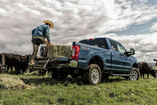 man using the tailgate step on a 2019 Ford Super Duty