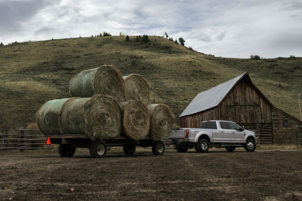 silver 2020 Ford F-350 Super Duty towing hay bales