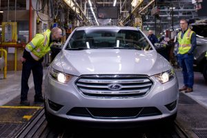 workers examining the last 2019 Ford Taurus