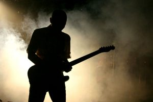 dark outline of a guitar player with fog in the background