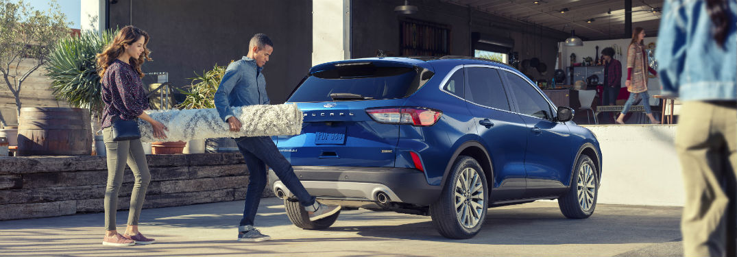 couple loading a rug into their blue 2020 Ford Escape