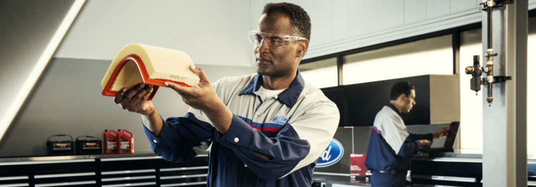 Ford service technician examining an air filter