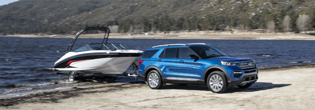 side view of a blue 2020 Ford Explorer Hybrid towing a boat