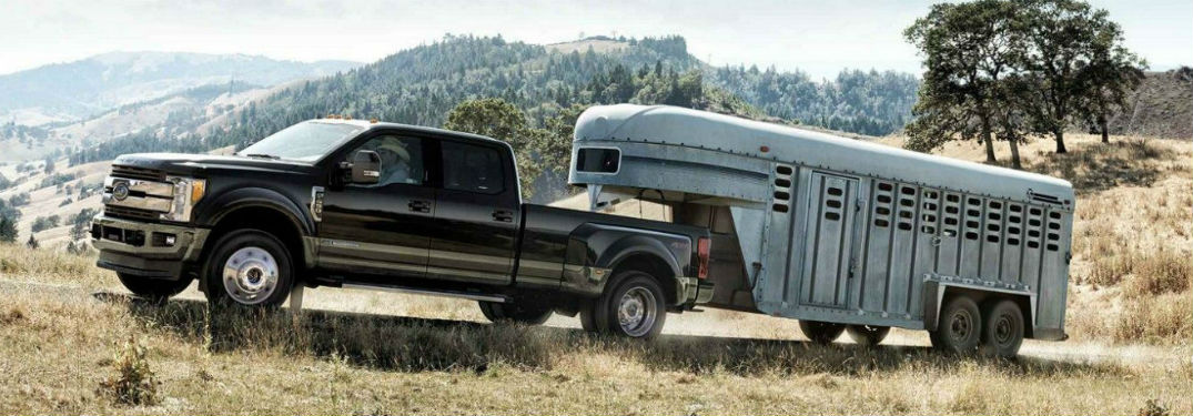side view of a black 2020 Ford Super Duty towing a horse trailer