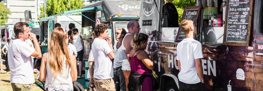 people waiting in line at a food truck