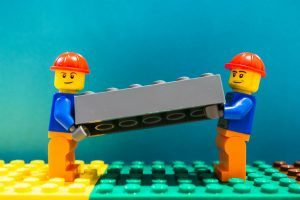 LEGO men carrying a brick