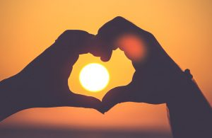 hands making a heart in front of the sun