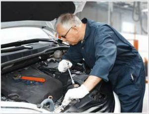 Ford technician checking under the hood of a car