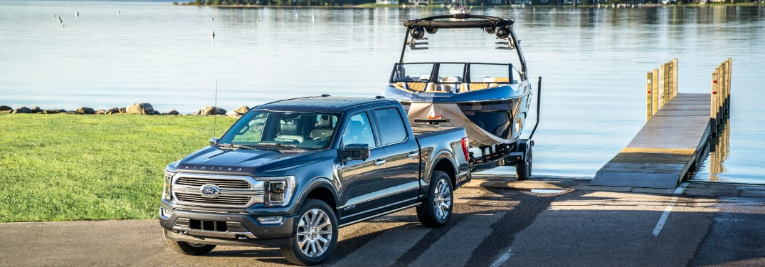 front view of a blue 2021 Ford F-150 towing a boat