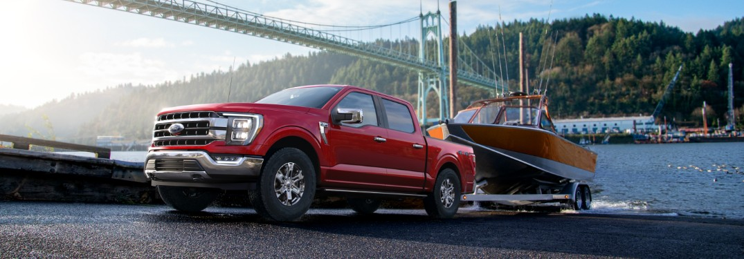 side view of a red 2021 Ford F-150 towing a boat