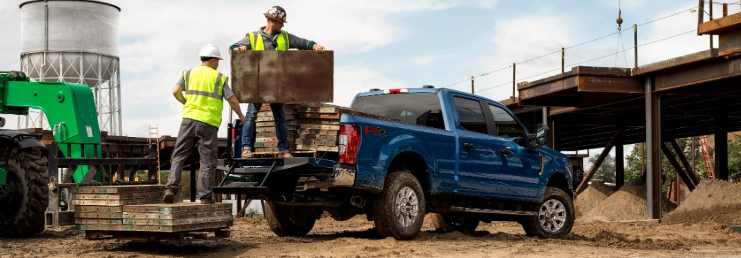 loading up the cargo bed of a blue 2021 Ford Super Duty