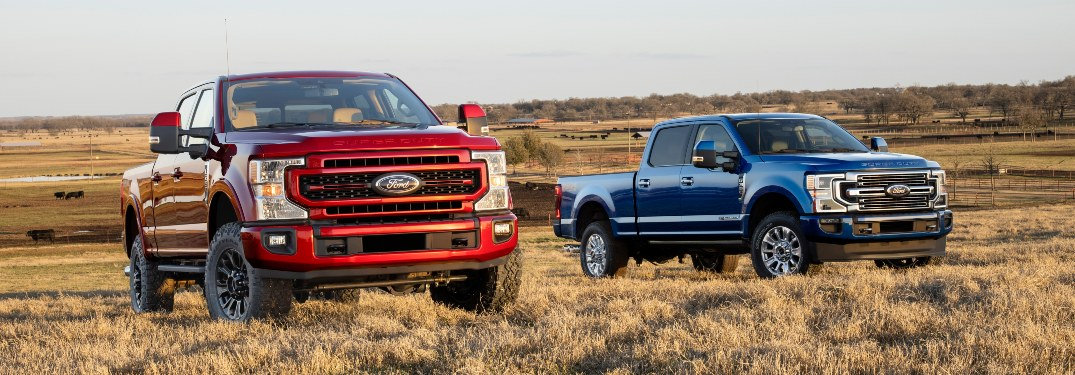 two 2022 Ford Super Duty trucks in a field