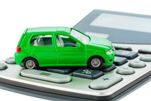 green toy car sitting on a calculator