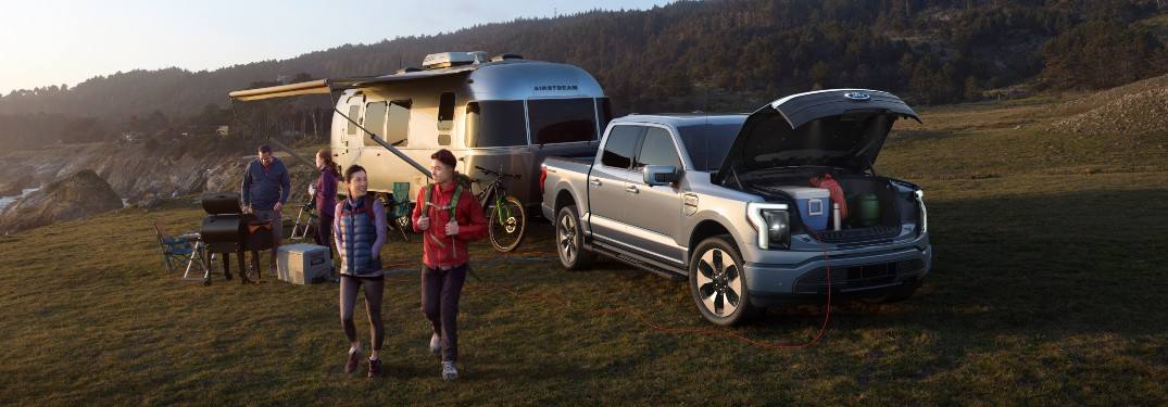 family camping with a 2022 Ford F-150 Lightning with its front trunk open