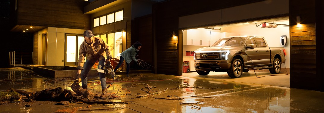 family cleaning up debris with lights powered by a 2022 Ford F-150 Lightning