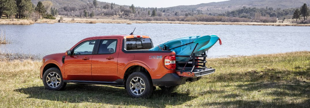 side view of a red 2022 Ford Maverick hauling a kayak