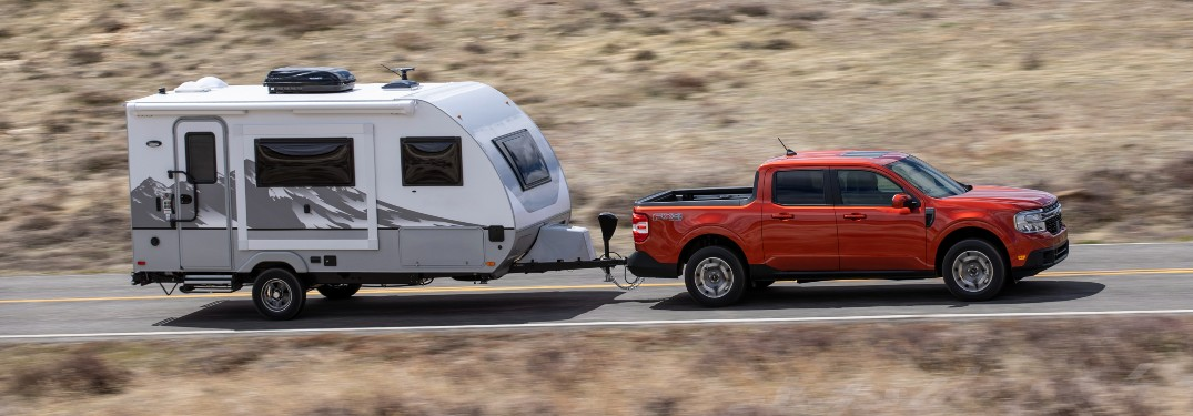 side view of a red 2022 Ford Maverick towing a camper