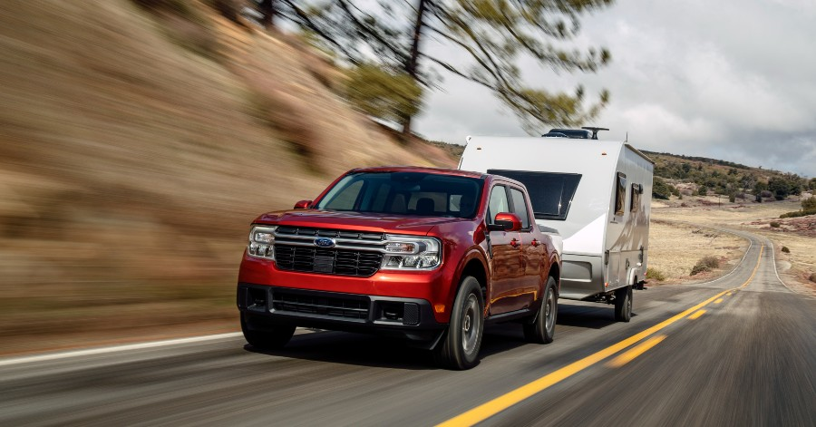 front view of a red 2022 Ford Maverick towing a camper