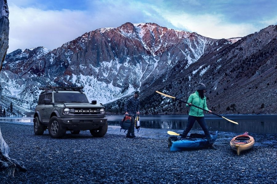 2021 Ford Bronco Front View Parked near a river with a snow-clad mountain in the background