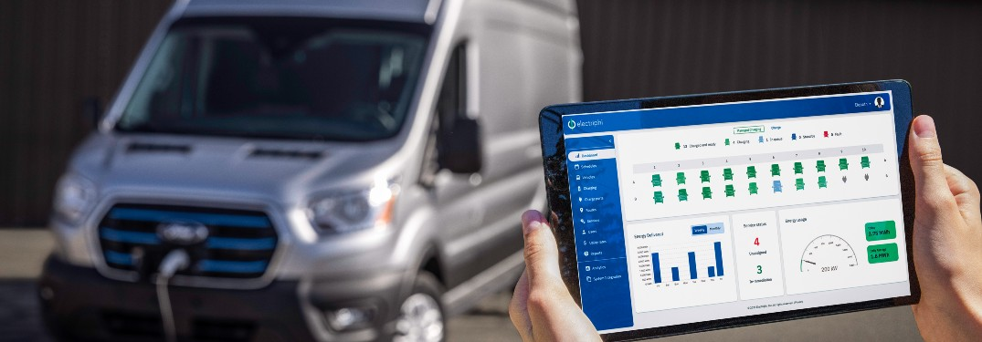 hand holding a tablet with a silver Ford Transit charging in the background