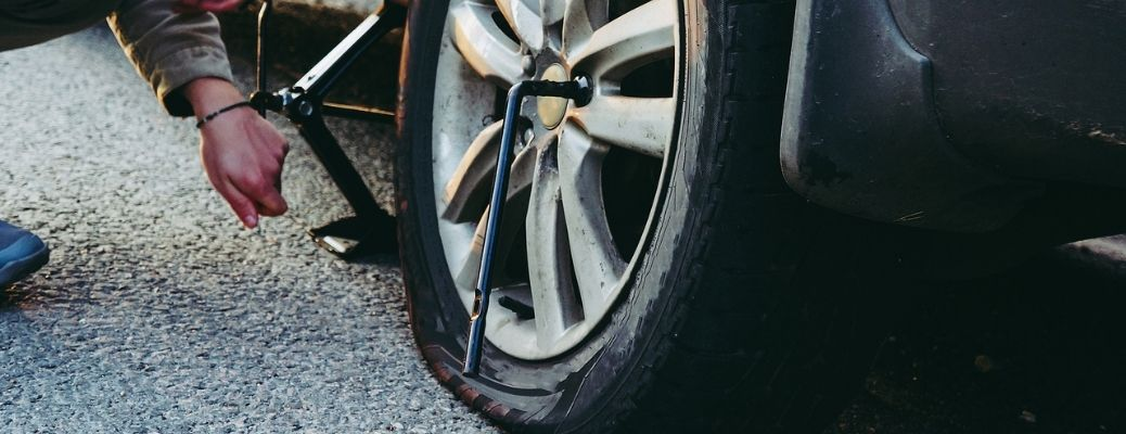 Image of a flat tire, a lug wrench and a jack