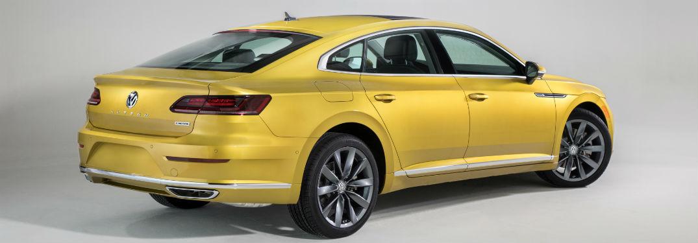 Passenger rear quarter panel exterior view of a yellow 2019 VW Arteon