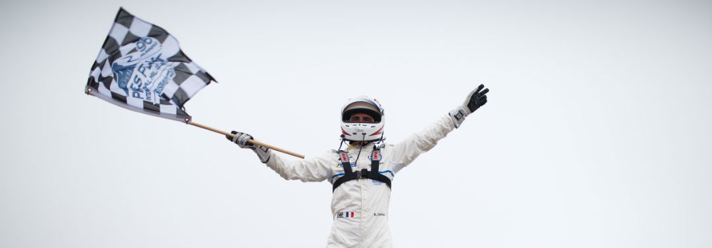 Racecar driver Romain Dumas holding the checkered flag