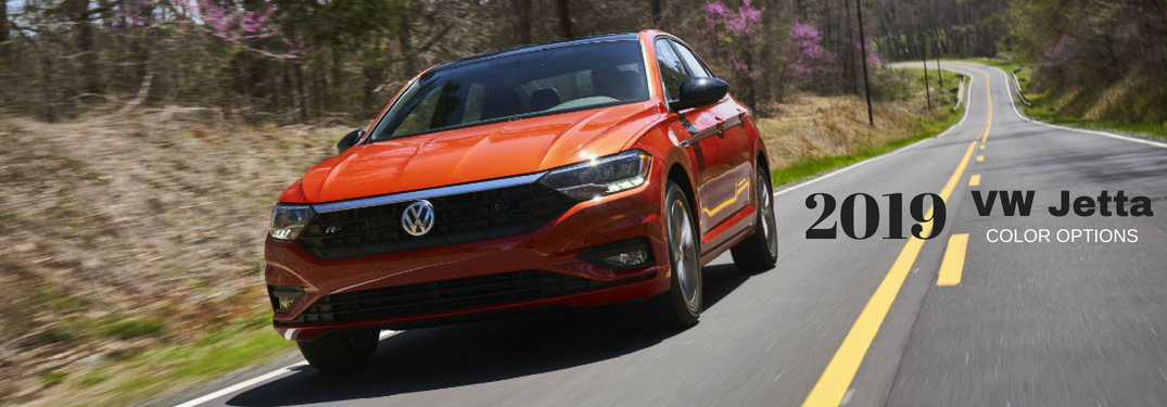 2019 VW Jetta Color Options, text on a front exterior image of an orange 2019 VW Jetta