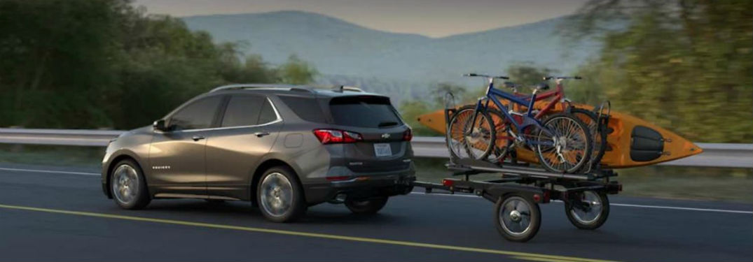 2018 Chevrolet Equinox Driving Alongside Water With A Small Trailer In Tow
