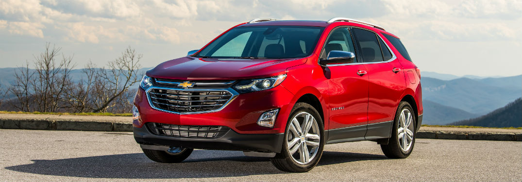 red 2018 Chevrolet Equinox parked on a hill in front of more hills