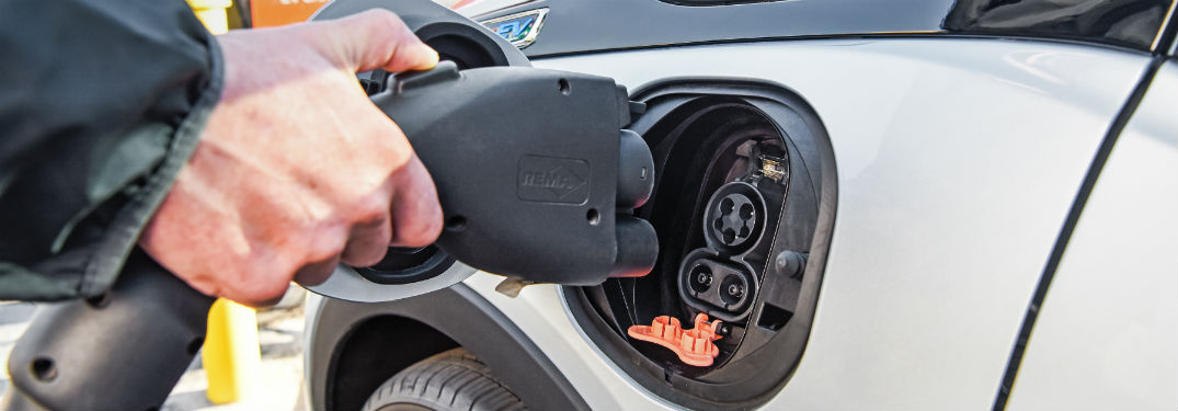 hand plugging cable into 2018 and 2019 chevrolet bolt ev