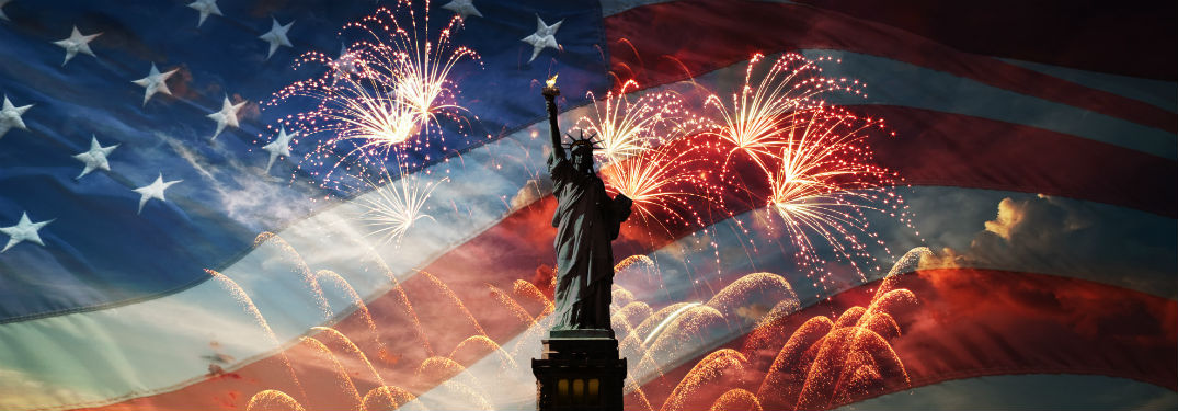 statue of liberty standing in front of fireworks and american flag