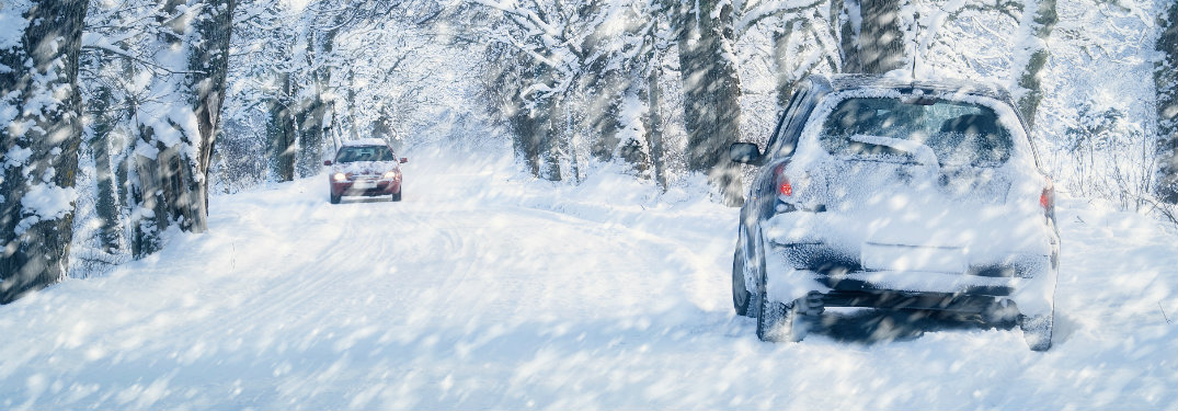 two cars on snowy road during blizzard
