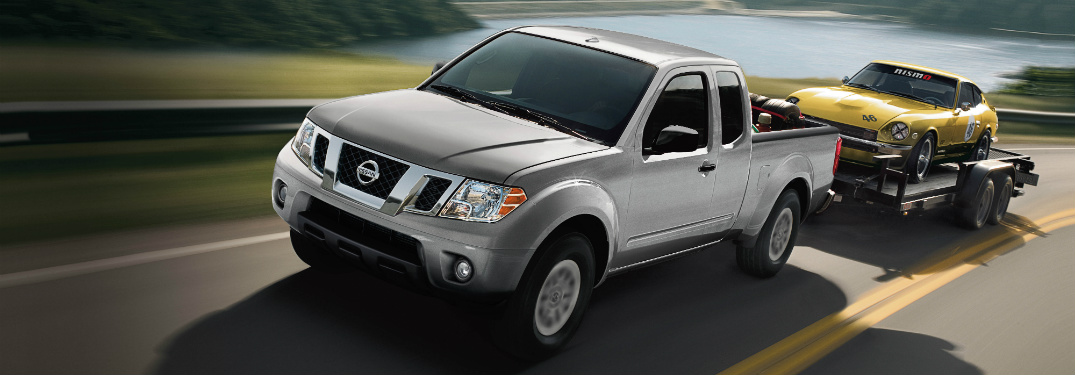 silver 2018 nissan frontier towing classic sports car on trailer