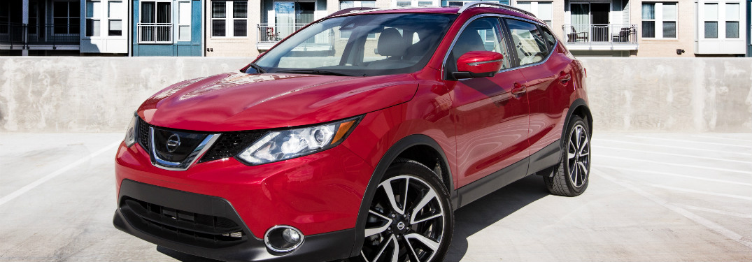 red 2018 nissan rogue sport parked in front of blue and white apartment building