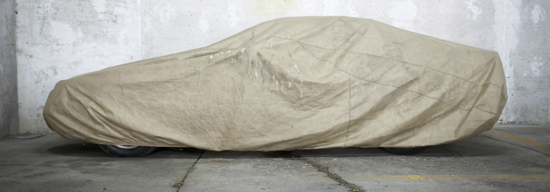car in empty garage covered with sheet