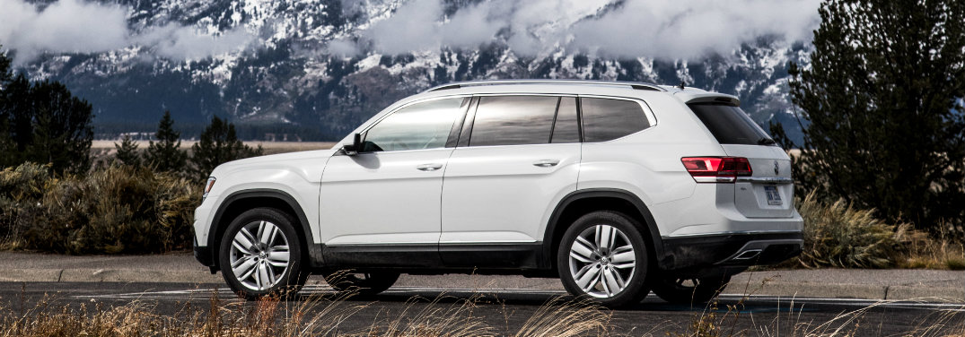 white volkswagen atlas parked in front of mountains